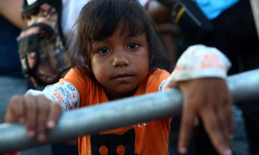 A migrant girl, traveling with a caravan of thousands from Central America en route to the United States, hitchhikes on a truck in Tapanatepec, Mexico.