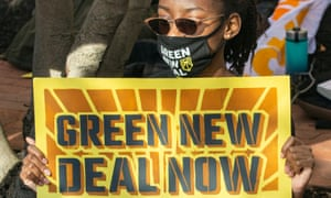 An activist holds a Green New Deal sign during a rally in Washington DC Thursday.