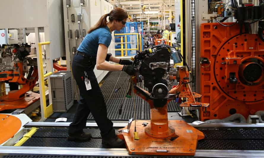 An employee works on an engine production line at a Ford factory.