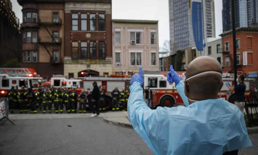 Firefighters gather to applaud medical workers outside Brooklyn Hospital Center in New York on Tuesday evening