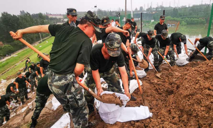 China's paramilitary police officers reinforce a lake dyke following heavy rains which caused severe flooding near Zhengzhou city