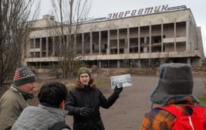 A tour guide holds up a photograph from before April 1986 to tourists attending a tour of Pripyat