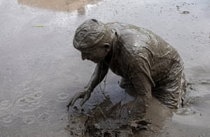 A person makes a splash in muddy water in a paddy field