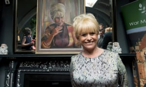 Dame Barbara Windsor standing with her portrait painted by Dan Llywelyn Hall
