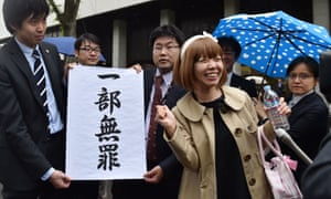 Megumi Igarashi and her lawyers pose with a sign reading 'a part is not guilty' in front of the Tokyo court on 9 May.