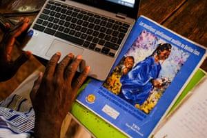 Ali Tapsoba works on his laptop