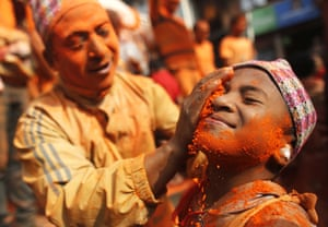 A Nepalese man smears his friend with vermillion powder