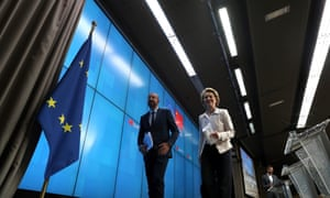 Michel and von der Leyen  walk off stage clutching papers smiling past EU flag.