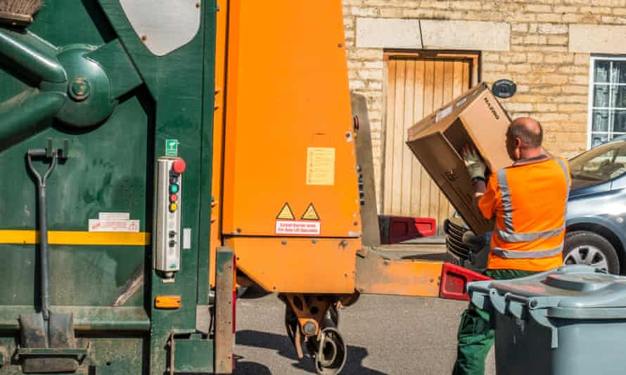 A council workman taking cardboard waste to a refuse lorry