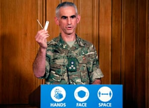 British Army Brigadier Joe Fossey, who is coordinating the mass coronavirus testing pilot in Liverpool, holds up the components of a lateral flow Covid-19 test as he speaks during a virtual press conference on the coronavirus pandemic in the UK inside 10 Downing Street in central London on November 9, 2020