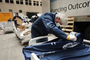 Workers prepare dozens of extra medical beds as they are delivered to Mount Sinai Hospital amid the coronavirus pandemic in New York City. Hospitals in New York City are facing shortages of beds, ventilators and protective equipment for medical staff.