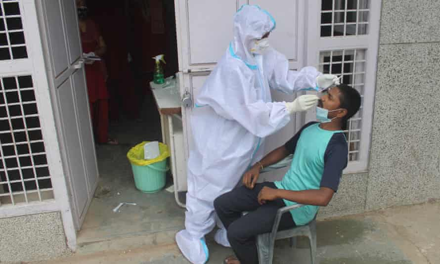 An Indian health worker tests for Covid-19 as inections in the country rise past 500,000.