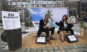 Oxfam activists in Brussels mimic wealthy people hiding their money to protest about the EU tax haven blacklist