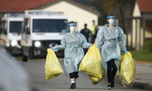 Two women in PPE with large full plastic bags