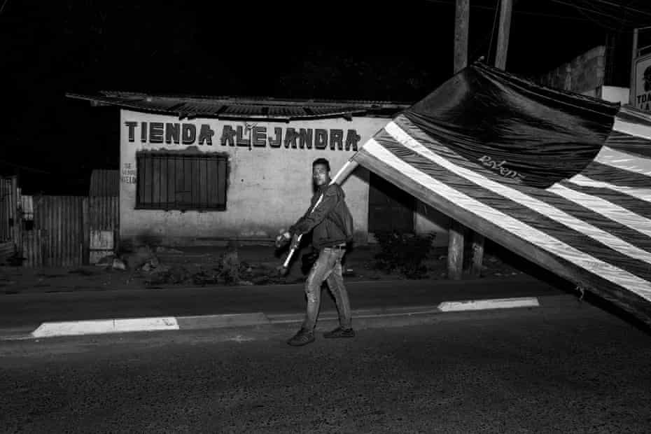 A member of the caravan carries a homemade US flag to show his enthusiasm to become an American citizen