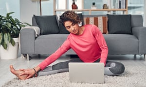 woman using a laptop while stretching in her living room