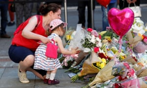 woman and girl leave flowers in Manchester