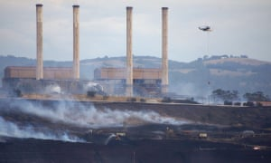 smoke blankets the surrounds of a coalmine and its chimneys