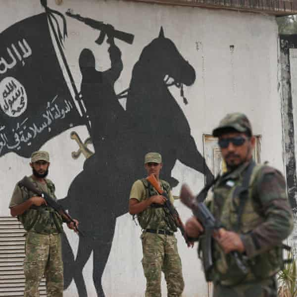 Members of Free Syrian Army stand in front of an Isis mural in Jarabulus.