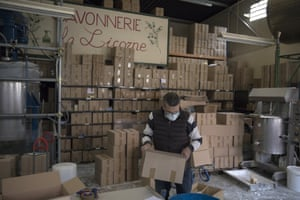 A factory worker prepares boxes to be packed with soap an hour before France's confinement measures went into effect