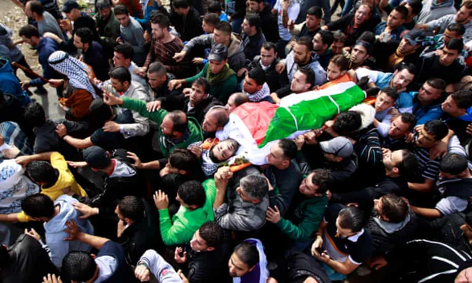 Palestinians carry the body of Anas al-Atrash during his funeral in Hebron, 8 November 2013