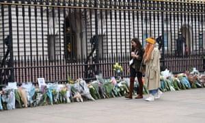 People walking past flower tributes outside Buckingham Palace.