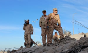 Libyan fighters stand atop the ruins of a house as they are close to securing last Isis holdouts in Sirte.