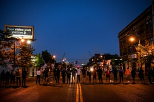 Protestors form a human chain in front of police officers near the 5th police precinct during a demonstration to call for justice for George Floyd