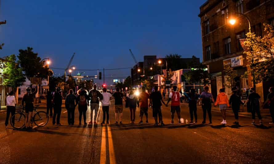 Protestors form a human chain in front of police officers near the 5th police precinct in Minneapolis