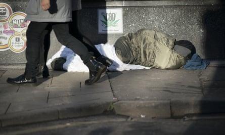 Man on street passing rough sleeper