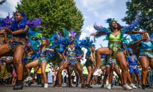Carnival performers dance through the streets