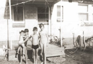 Four children standing in front of a suburban house in a black and white photograph