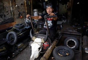 Yogi Hermawan Saifullah, the owner of a workshop that builds 'extreme' Vespas, poses on one of his designs at his shop in Kediri.