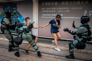 Police chase down a couple wearing facemasks in the central district in Hong Kong on October 5, 2019, a day after the city's leader outlawed face coverings at protests invoking colonial-era emergency powers not used for half a century.