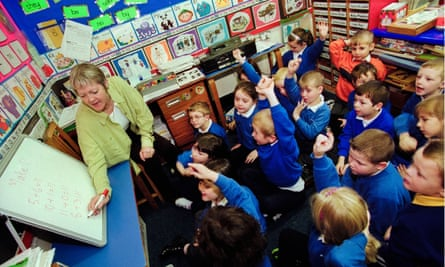 Pupils being taught maths by teacher in classroom of primary school