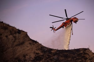 A fire department helicopter drops liquid to extinguish the Tick fire.