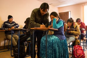 Elizabeth Ramos, 21, has her work checked by Prof Zénon Quispe during a class for her history degree at El Alto Public University