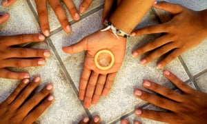 Hands of adolescents and condom