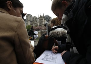 People draw sketches of the blackened shell of the Paris landmark
