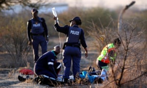 A paramedic receives help from a South African police officer as he tends to protesting mineworkers in Marikana, August 2012.