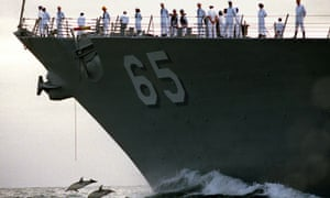 Dolphins in front of US Navy ship Benfold. Marine life will now be protected from Navy sonar.