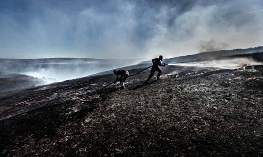 Firefighters tackle the wildfire on Saddleworth Moor
