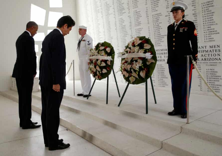 Barack Obama and Shinzo Abe laid wreaths and tossed flower petals into the water aboard the USS Arizona Memorial to honor those who died in Pearl Harbor.