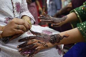 A beautician applies henna on the hands of a customer in Karachi, Pakistan