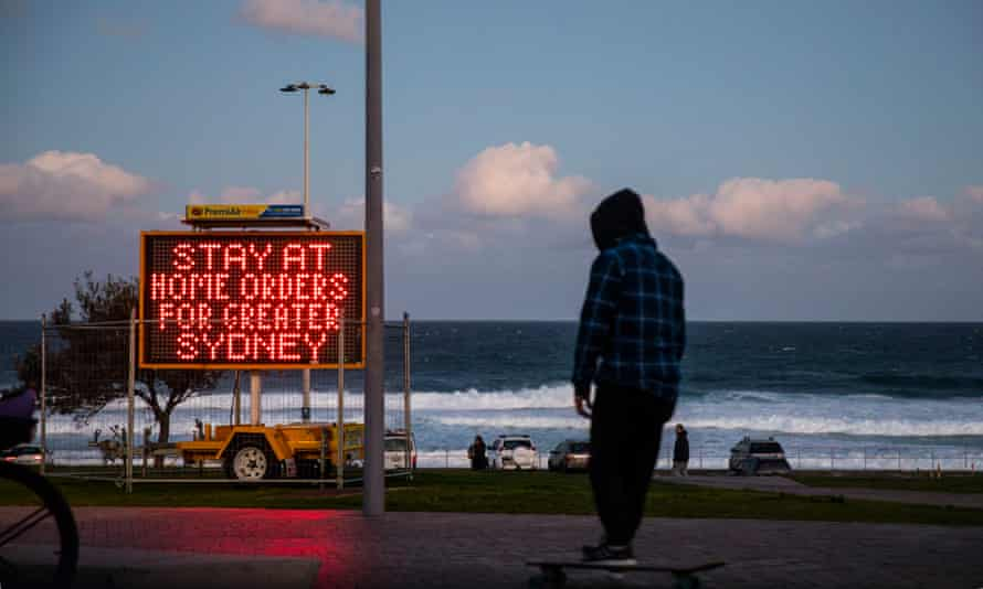 sign at bondi beach saying 'stay-at-home' orders for greater sydney