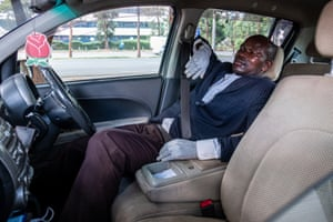 An Uber driver relaxes between journeys, still wearing his protective gloves