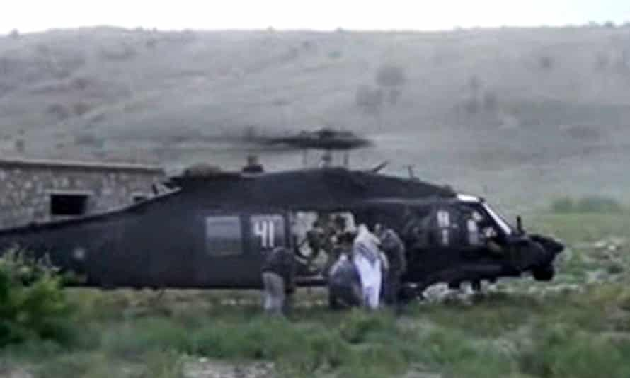 Men in civilian clothing lead sergeant Bowe Bergdahl, in white, towards a helicopter in eastern Afghanistan after he was handed over by Taliban forces.