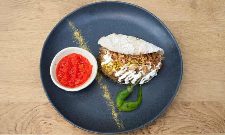 Celeriac Schwarma inside a pitta bread, with a bowl on fermented chilli, on a round black plate