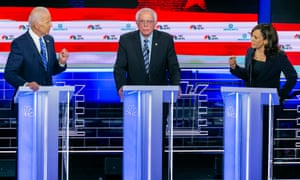Kamala Harris, right, speaks to Joe Biden, left, as Bernie Sanders looks on during the second night of the first Democratic presidential debate on 27 June 2019.