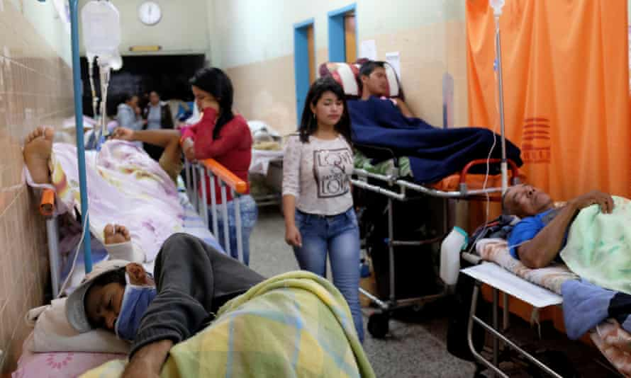Patients lie on beds in an aisle of the emergency room at the University Hospital in Merida, Venezuela